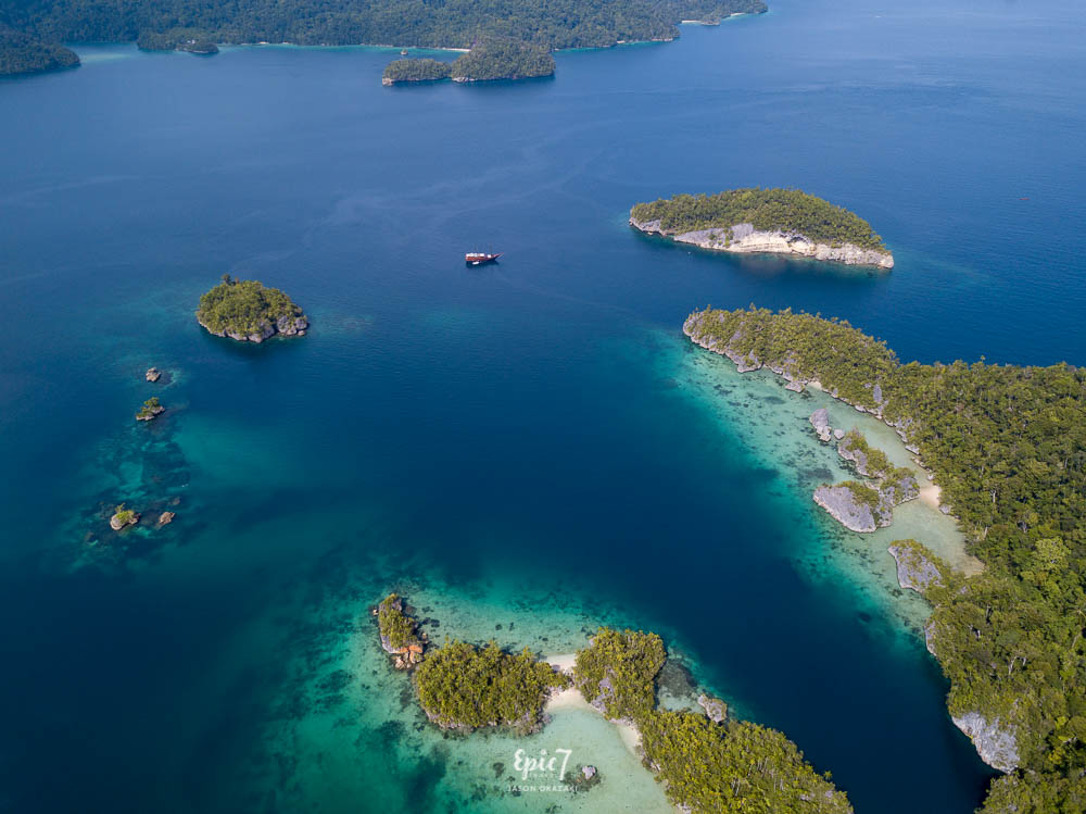 aerial view dive damai liveaboard anchored in raja ampat