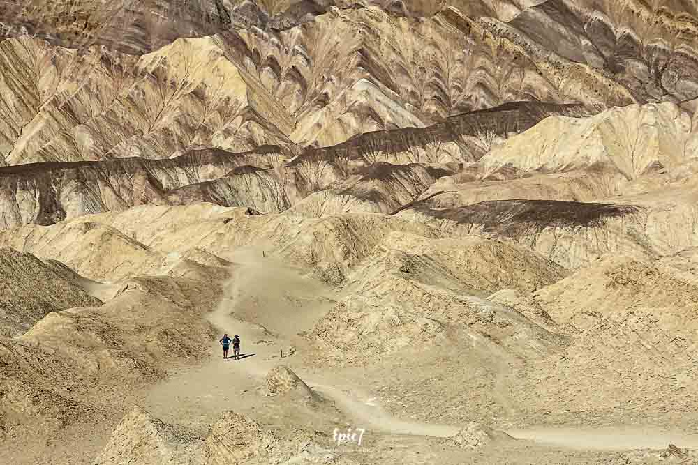 People hiking through the Badlands on the Golden Canyon Gower Gulch Death Valley Hike
